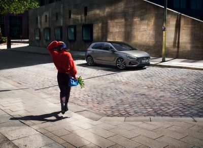 Woman walking towards the new i30 Hatchback parked in a street.
