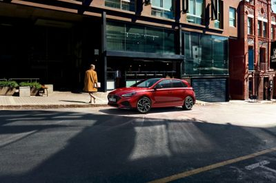 The new i30 N Line Hatchback parking on a street next to a glass front.