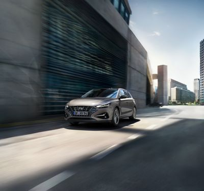 The new Hyundai i30 drivig in a concrete street.